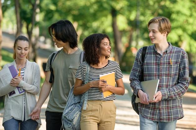 話しながら歩いている若い幸せな学生。よそ見。