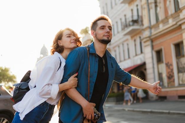 恋人たちの若い幸せなスタイリッシュなカップルは、街で車をキャッチします。ヒッチハイクのコンセプト