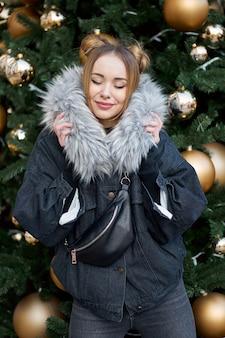 金色のボールとクリスマスツリーの近くに目を閉じて若い幸せなスタイリッシュな女性