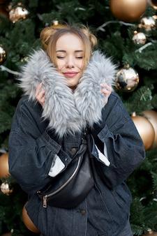 골든 볼 크리스마스 트리의 배경에 닫힌 된 눈을 가진 젊은 행복 세련 된 여자.