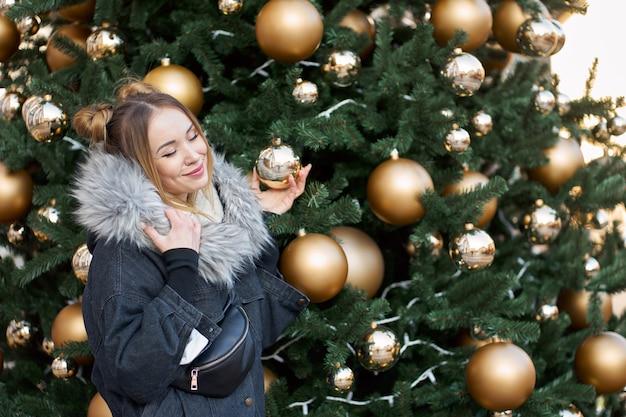 골든 볼 크리스마스 트리 배경에 포즈 닫힌 된 눈을 가진 젊은 행복 세련 된 여자.