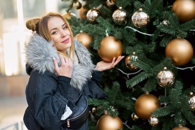 金色のボールとクリスマスツリーの近くでポーズかわいい髪型の若い幸せなスタイリッシュな女性