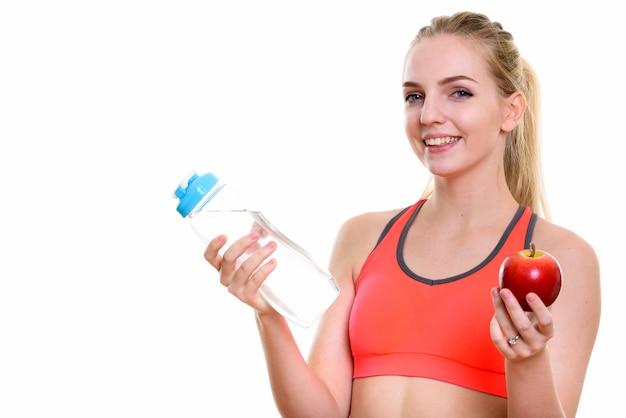 水のボトルと赤いリンゴを持って笑っている若い幸せな10代の少女