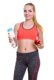 水のボトルを保持しながら笑顔の若い幸せな10代の少女