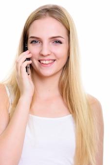 電話で話している間笑顔の若い幸せな10代の女性