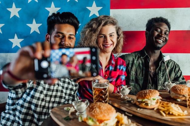 Молодые, счастливые трое друзей в ресторане быстрого питания делают селфи, пока едят гамбургеры и пьют пиво