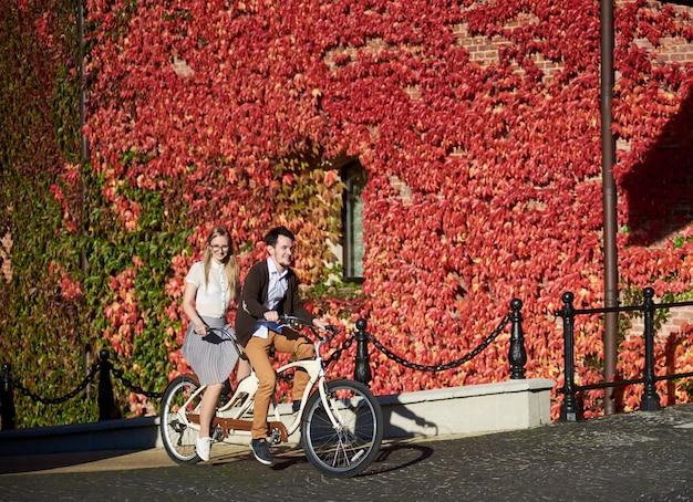 若い幸せな観光カップル、ハンサムな男、明るい晴れた秋の日にかなり長い髪の金髪女性サイクリングタンデムバイク