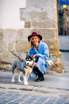 Young happy tourist girl with happy smile in a blue coat and burgundy hat with young dog breed husky in the street