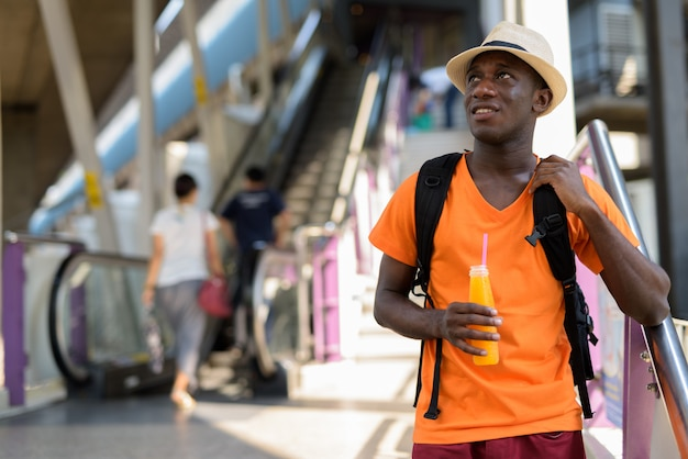 Young happy tourist man smiling while thinking and holding orange juice against view of escalator in the train station of bangkok thailand