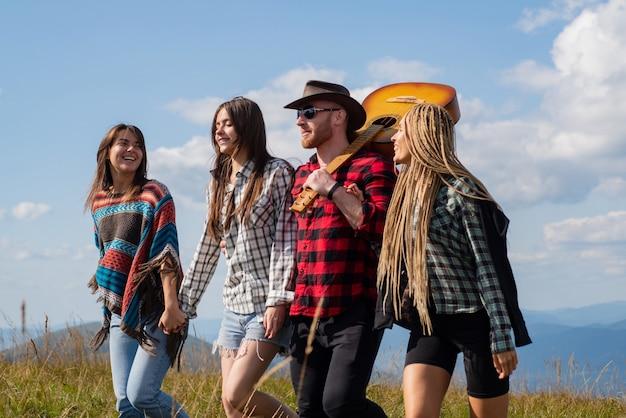 幸せな若い友達を楽しんでいる山の若い幸せな観光客は、金の自然グループで素敵な一日を楽しんでいます...