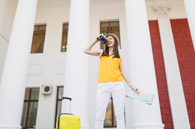 Молодая счастливая туристическая женщина путешественника в повседневной одежде с чемоданом, карта города фотографирует на открытом воздухе ретро винтаж фотоаппаратом. девушка выезжает за границу на выходные. туризм путешествие образ жизни.