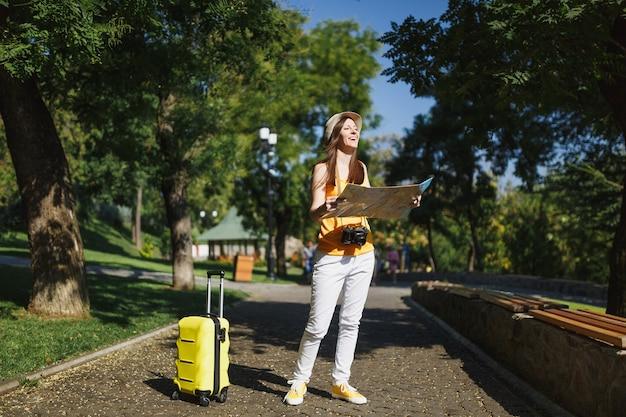 黄色の夏のカジュアルな服を着た若い幸せな旅行者の観光客の女性、スーツケースの都市地図の帽子は、屋外の街を歩きます。週末の休暇に旅行するために海外に旅行している女の子。観光の旅のライフスタイル。