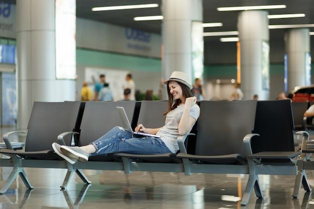 ラップトップに取り組んで、勝者のジェスチャーをして、国際空港のロビーホールで待っている若い幸せな旅行者観光客の女性