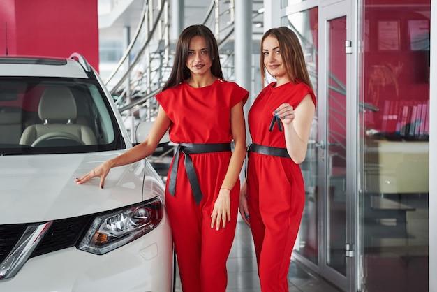 Молодая счастливая женщина 2 около автомобиля с ключами в руке - концепция покупая автомобиля.