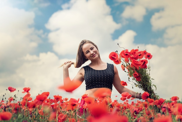 ポピーの花の花束を持って歩いて、フィールドで晴れた日を楽しむ若い幸せなウクライナの女性