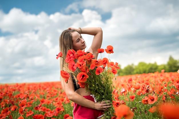 양 귀 비 꽃의 꽃다발을 들고 젊은 행복 우크라이나 여자 산책과 필드에서 화창한 날을 즐길 수