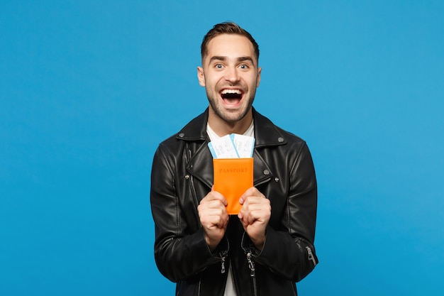 Young happy unshaven man in black jacket white t-shirt hold in hand passport tickets isolated on blue wall background. passenger traveling abroad getaway. air flight journey concept mock up copy space