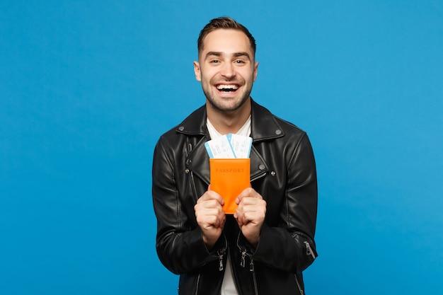 검은 재킷 흰색 티셔츠를 입은 젊은 행복한 면도하지 않은 남자는 파란색 벽 배경에 격리된 여권 티켓을 손에 들고 있습니다. 해외 여행을 떠나는 승객. 항공 비행 여행 개념 모의 복사 공간