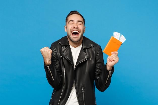 Молодой счастливый небритый человек в черной куртке белой футболке держит в руках паспортные билеты, изолированные на синем фоне стены. пассажир выезжает за границу. концепция путешествия по воздуху макет копией пространства