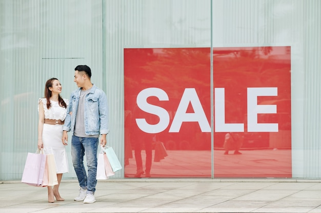 Young happy vietnamese couple with shopping bags standing at big sale banner outside the shopping mall