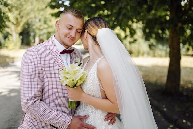 Giovani sposi felici. abbraccio caucasico dello sposo e della sposa