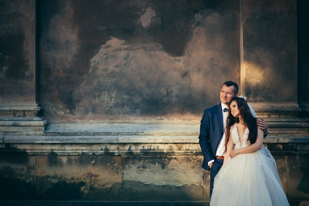 秋の城と湖の背景に抱き合ってキスする若い幸せな結婚式のカップル