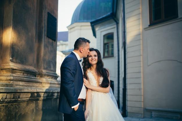 城の背景に抱き合ったりキスしたりする若い幸せな結婚式のカップル