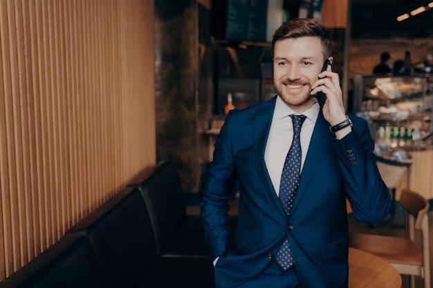 Молодой счастливый ухоженный привлекательный бородатый опытный банкир в стильном пиджаке разговаривает по мобильному телефону с улыбкой, стоя в кафе-баре в ожидании встречи с деловыми партнерами
