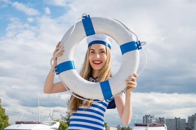 彼女の手で救命浮環でポーズをとってヨットの上に立っている青い縞模様のドレスで若い幸せな女性の外観