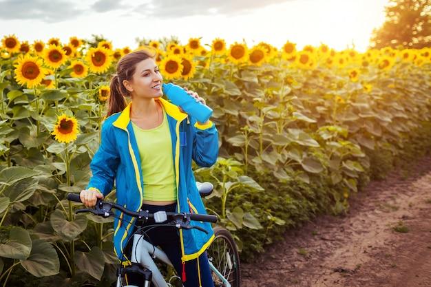 ひまわり畑に乗った後若い幸せな女自転車乗り飲料水。夏のスポーツ
