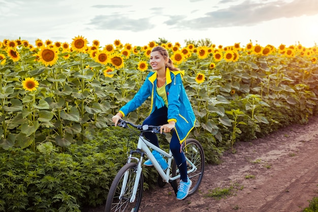 Young happy woman bicyclist riding bicycle in sunflower field.