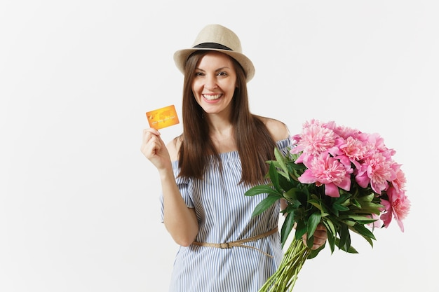 Young happy woman in blue dress, hat holding credit bank card, money, bouquet of beautiful pink peonies flowers isolated on white background. business, delivery, online shopping concept. copy space.