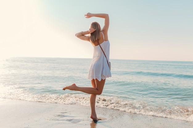Молодая счастливая женщина танцует, поворачиваясь на берегу моря в солнечном летнем стиле моды в белом платье на каникулах
