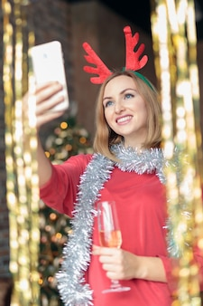 Young happy woman drinking champagne and taking selfie at new year's party