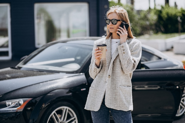 Young happy woman drinking coffee by the car
