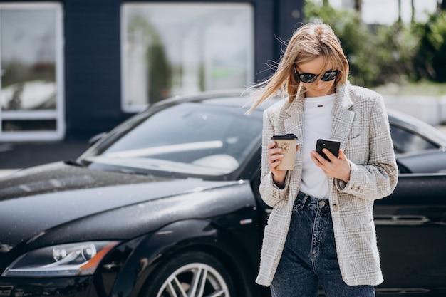 Молодая счастливая женщина пьет кофе на машине