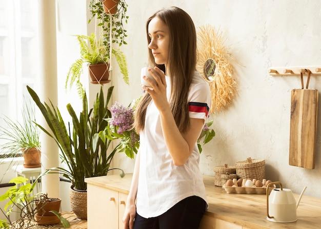 朝のキッチンでコーヒーを飲む若い幸せな女性。
