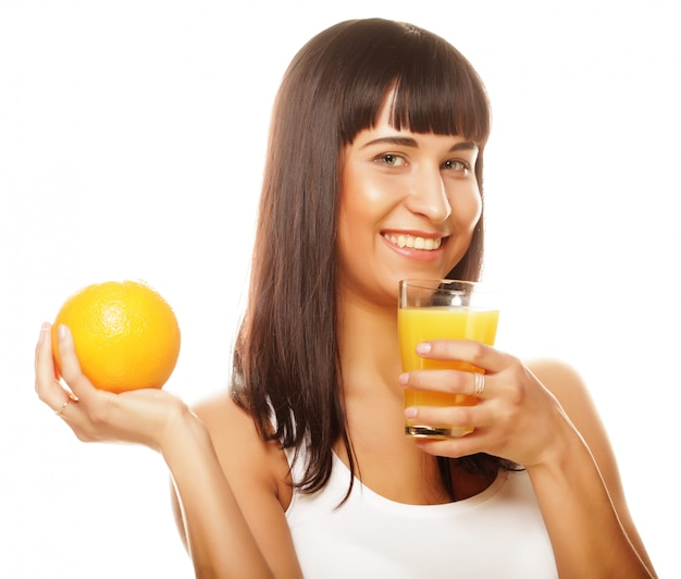 Young happy woman drinking orange juice