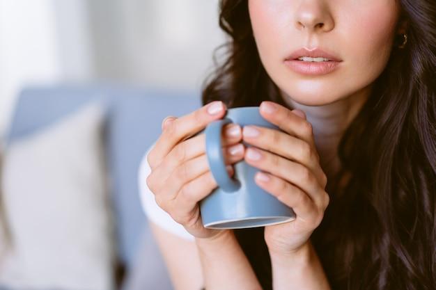 차를 마시고 밝은 아파트에서 소파에 앉아 꿈을 꾸고 젊은 행복 한 여자.
