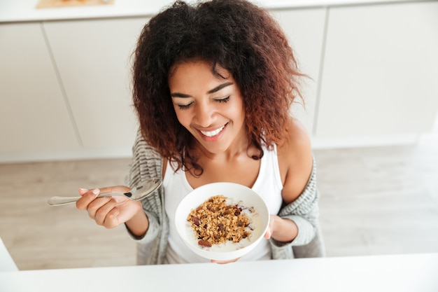 Young happy woman eating breakfast in kitchen