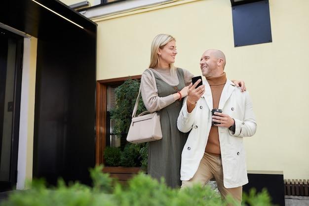 夫を抱きしめて街で一緒に楽しい時間を過ごす若い幸せな女性