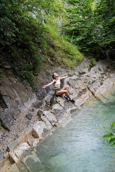 Young happy woman enjoing the nature, sitting by the mountain river.
