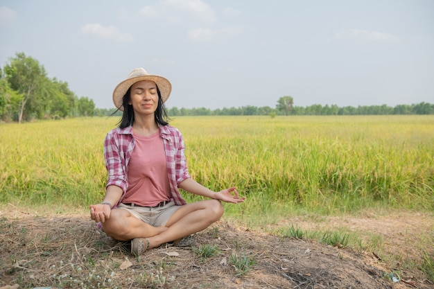 Young happy woman enjoying and meditating with the lovely view of the rice terrace in thailand, asian. travel photograph. lifestyle. woman sitting at rice field outdoors practicing yoga relaxation.