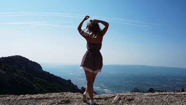 Молодая счастливая женщина, наслаждаясь великолепным видом на горы монсеррат