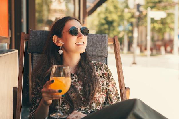 若い幸せな女性は、テラスに座って屋外で彼女のモクテルを楽しんでいます。