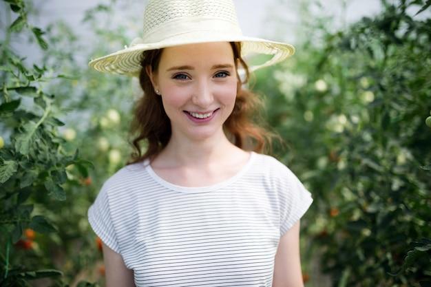 彼女の温室で働く若い幸せな女性の農夫
