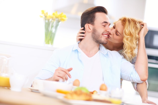 Young happy woman giving good morning kiss to her husband