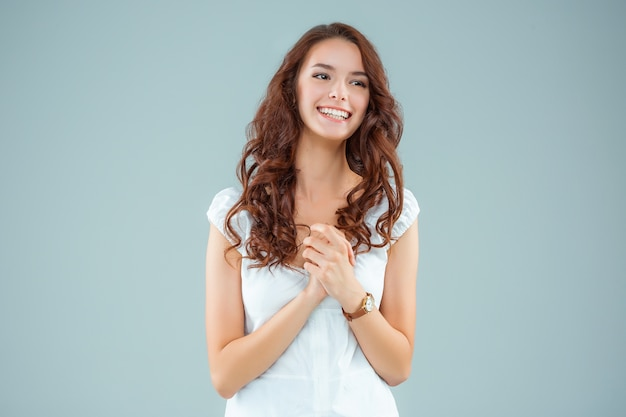 La giovane donna felice su grigio
