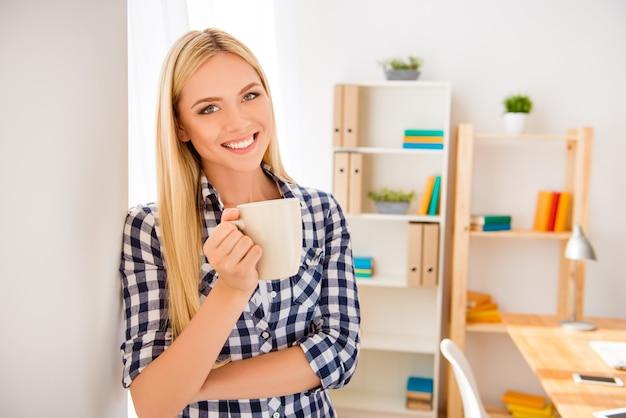 休憩とコーヒーを飲む若い幸せな女性