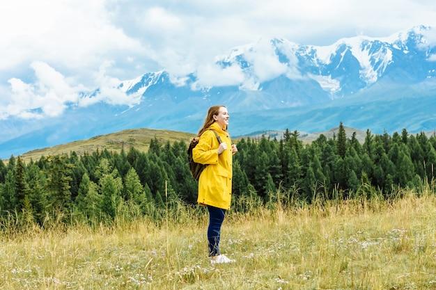 배낭 젊은 행복 한 여자 등산객 휴가에 눈 덮인 산의 배경에 선다. 여행 및 자연 여행 개념